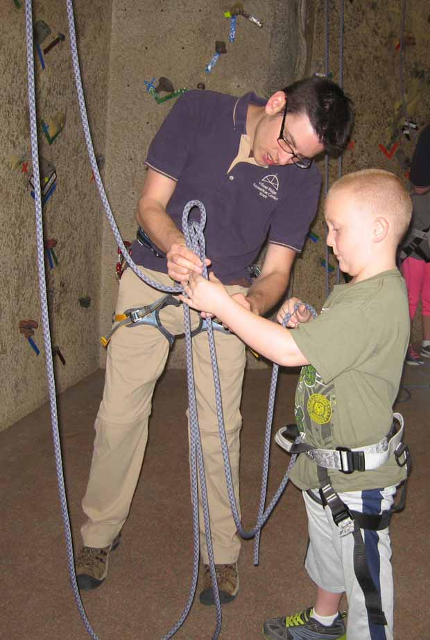 Climbing Staff teaching young boy how to tie a rope